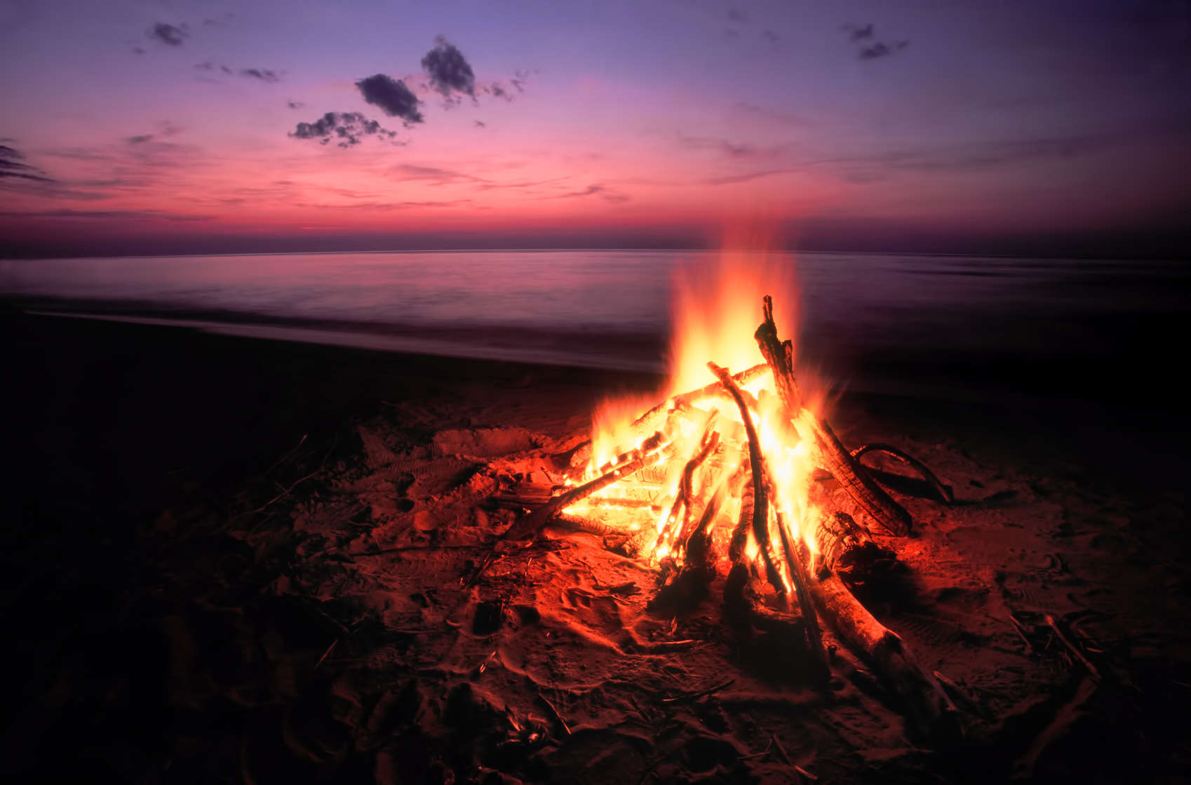 Blazing campfire at sunset along the beautiful beach of Lake Superior in northern Michigan.