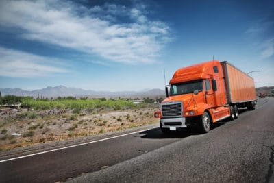 Large orange truck transporting goods on the freeway in the desert