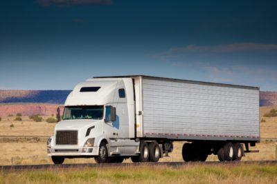 truck driving down a desert highway